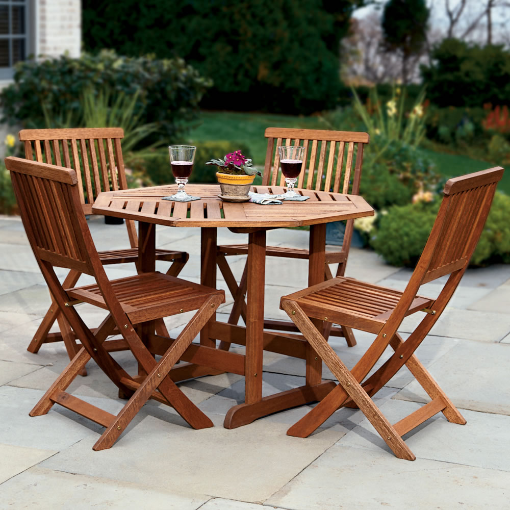 The trestle patio table and stow away chairs hammacher for Deck table and chairs